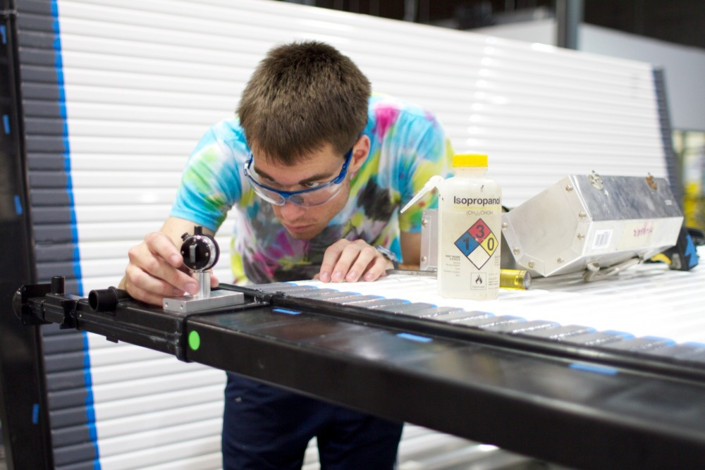 Senior civil engineering major Dan Grannes performs a final inspection on a neutrino detector module Thursday at the NOvA project's Como warehouse.  After passing inspection, the panels will be shipped to the Fermi National Accelerator Laboratory in Illinois.