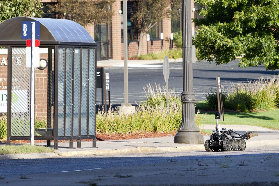 A St. Paul bomb squad robot removes the suspicious package from a bus stop Saturday near University Avenue West and Barry Street.