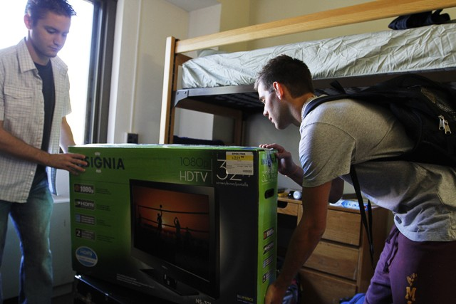 Steve Cunningham, left, and Aaron Gahwileer carry a TV into their new room Tuesday in Territorial Hall.
