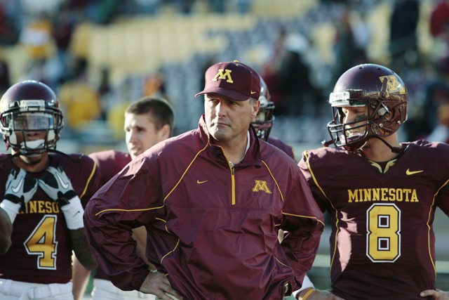 Gophers head coach Tim Brewster (left) and senior quarterback Adam Webber stand with their team after losing to the University of Southern California Trojans 32-21 Saturday at TCF Bank Stadium.