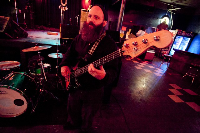 Bass player Jon Davis warms up late Saturday night before his band Haunted House played at the Turf club.