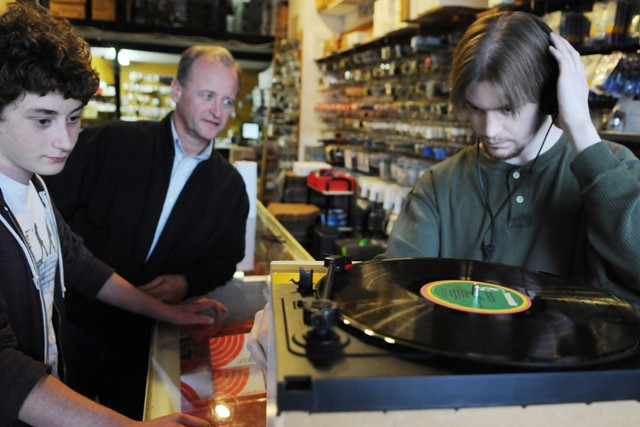 Osseo High School junior Jordan Limmer, left, waits along with his father, Warren Limmer, center, as Needle Doctor employee Matthew Randall checks the speed of their turntable Friday at the store.  The Warrens made the drive from Maple Grove to the Dinkytown for the visit.