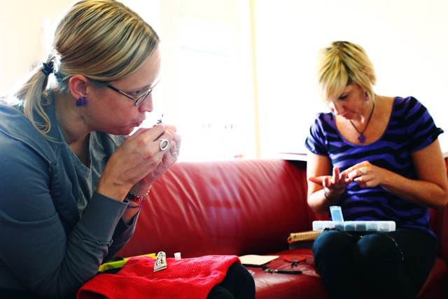 Rachelle Thorpe, left, and Hollie Olson, right, work in Olson's apartment Sunday morning in Uptown. Thorpe and Olson use recycled bike parts to make jewelry for their new business Split Personality designs.
