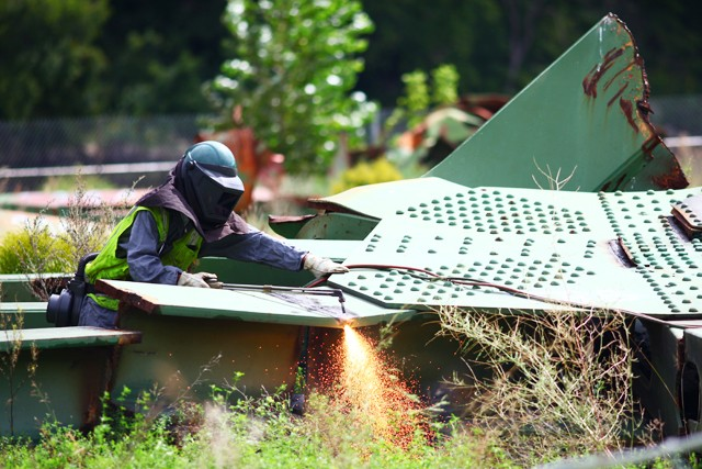 Dan Maher operates a cutting torch Tuesday morning at Bohemian Flats. Workers from Bolander & Sons are helping with clean-up of the 35w bridge wreckage.