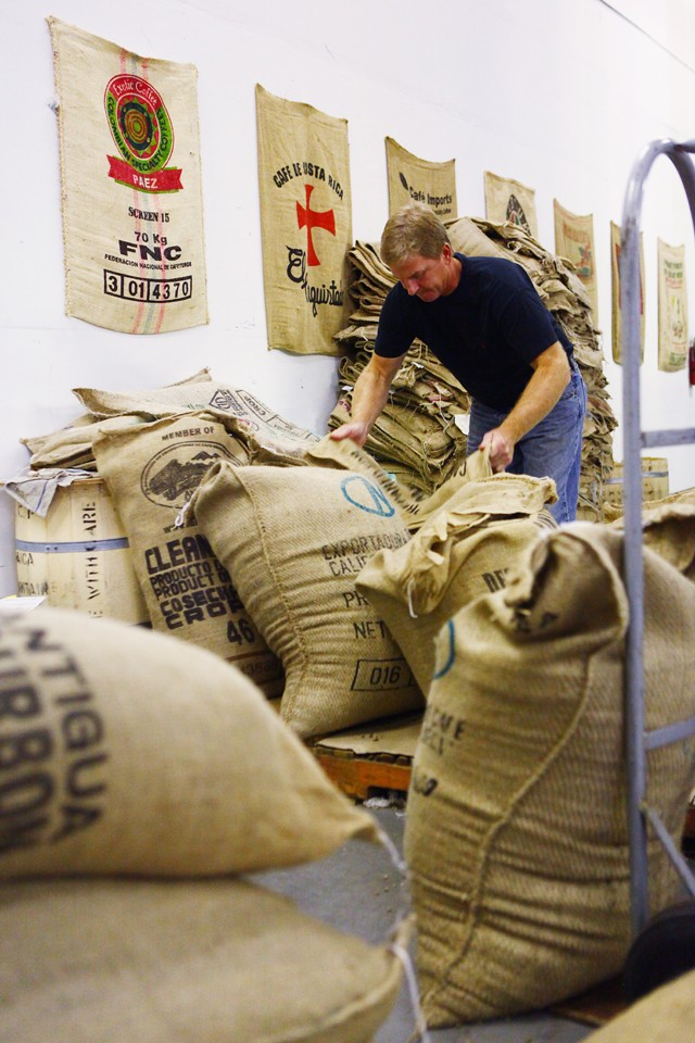 Kevin Larson lifts a bag of raw coffee beans to be put in the roaster.