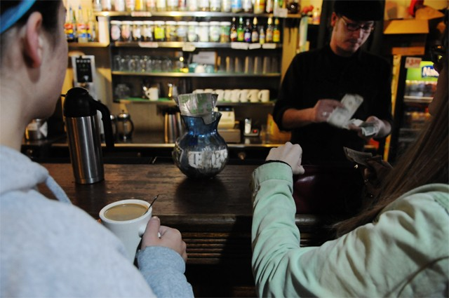 Finance and non-profit management senior Roxy Dreyer (left) and Spanish and anthropology senior Trisha Netsch, (right) purchase coffee from barista Jason Buckendorf Sunday at Hard Times Café.