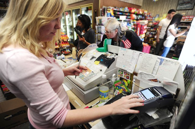 Employee Staci Caldow processes a credit card Friday afternoon at House of Hanson.