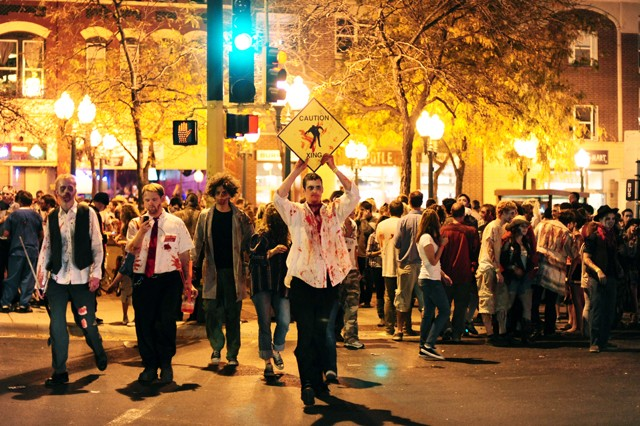 Josh Ludwig safely leads his fellow zombies across the street Saturday night at Seven Corners.