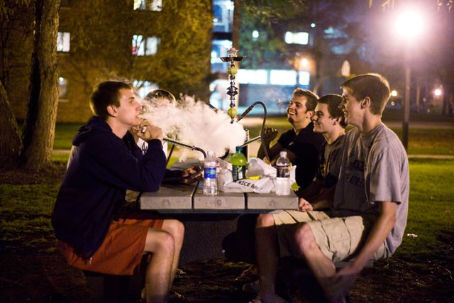 Freshman students try out their new hookah on their dorm lawn.