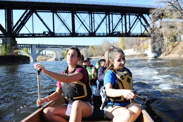 Juniors Katie Duffy (left) and Alyssa Sajady  row their canoe back to shore Friday afternoon in the Mississippi River.  The canoe event was one of many in the first ever Gopher Adventure Race.
