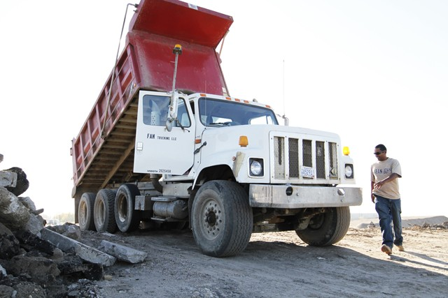 Chandrashaker Bhagwandin dumps a load of road material from the Central Corridor construction site in Inver Grove Heights on Tuesday.