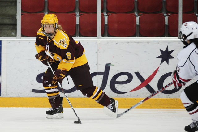 Freshman Sarah Davis looks to pass Friday night at the National Hockey Center in St. Cloud.  Davis had 1 of the 5 goals in the Gopher's win over the Huskies.