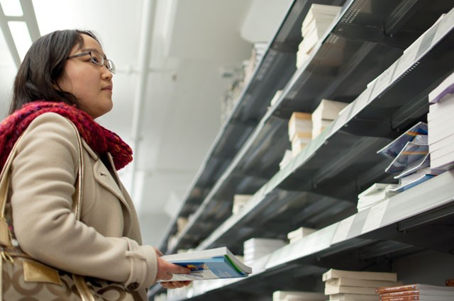 Jie Hye, a Univeristy of Minnesota student in the English as a Second Language Program, shops for books on Monday in Coffman Bookstore.  Soon we may start to see more people buying electronic versions of their textbooks and less people in buying the paper versions.