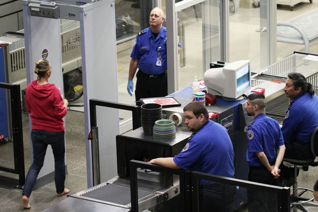 TSA employees wave people through the security scanner Friday evening at the Minneapolis- St.Paul International Airport. The scanner is part of a new process using Advanced Imaging Technology to screen for both metallic and non-metallic objects.