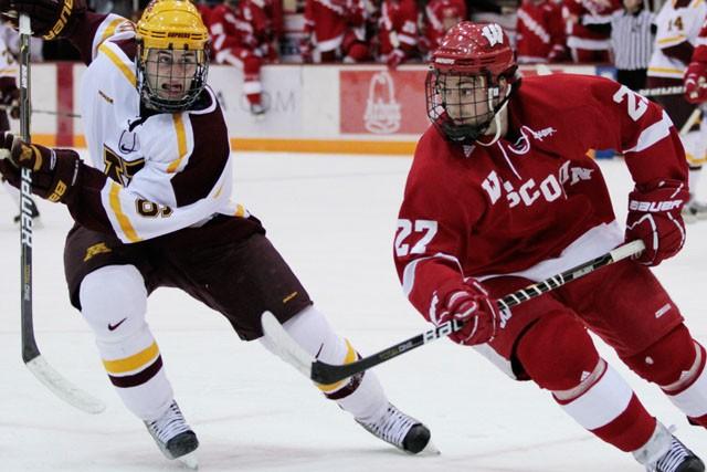 Freshman Nate Condon races University of Wisconsin Defenseman Frankie Simonelli  for the puck Friday at Mariucci Arena.