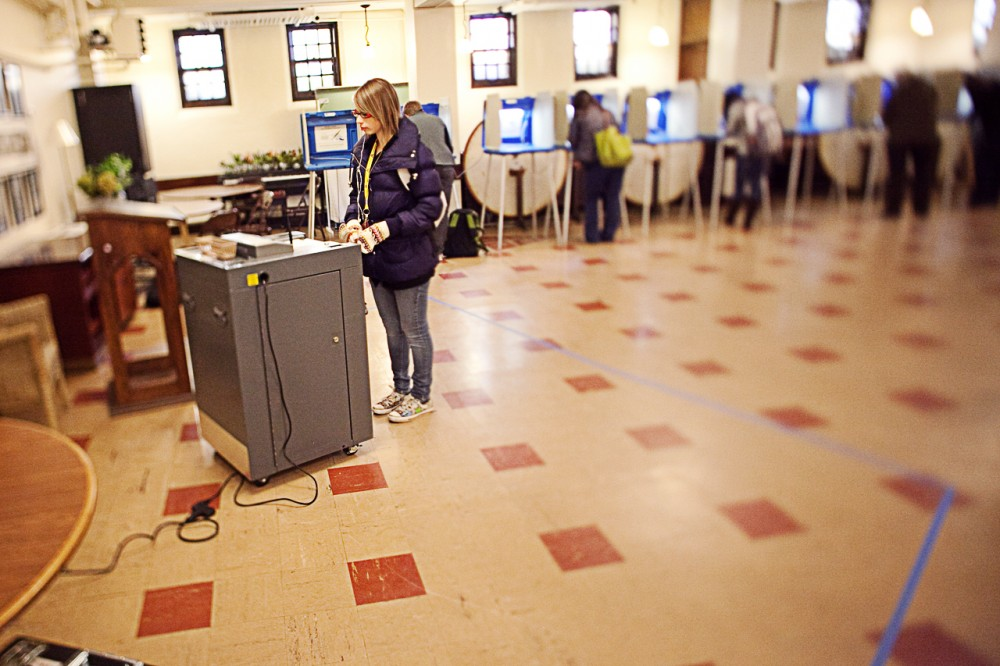 Freshman Brenna Thom places her ballot into the ballot counter Tuesday morning at Grace University Lutheran Church.
