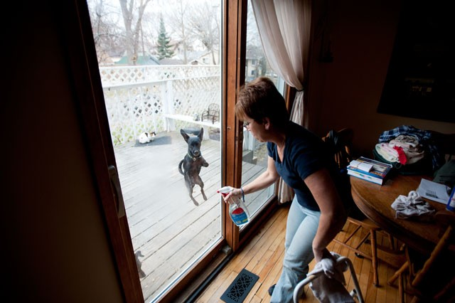 Joni Hahn washes the windows on Wednesday in her St. Paul home. Hahn's case against the University alleging malpractice in the care of her husband was dismissed in 2008.