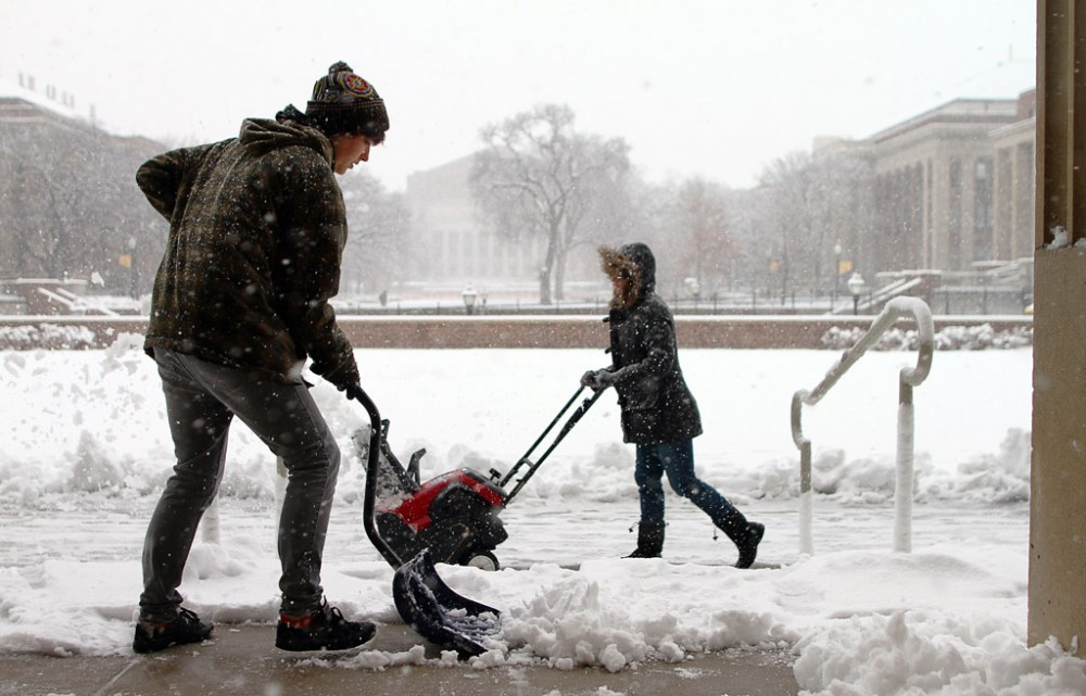 University student Madeline Lee shovels snow Saturday in front of Coffman Union where she works. Lee said she had shoveled the front steps several times that morning.