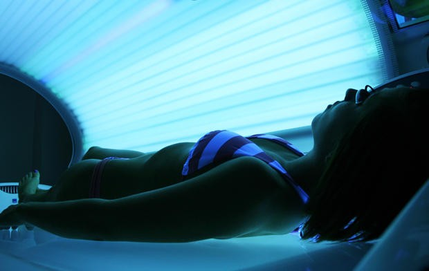 MCTC senior Stephanie Johnson lies in a tanning bed at Darque Tan in Stadium Village on Tuesday. A 10 percent tax on indoor tanning services is part of the U.S. Senate's health care reform proposal.