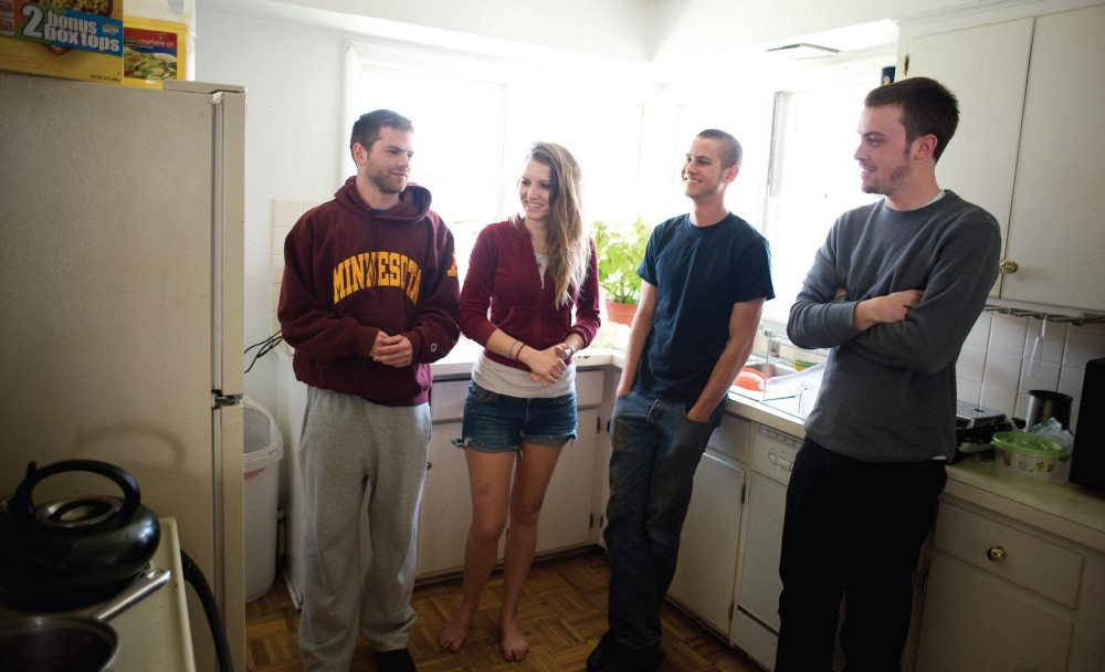 Neil, Caleb and Robbie stand in their kitchen with Caroline on Saturday in Marcy-Holmes. Neil, Caleb and Robbie are three of five occupants living in the house, which is zoned to allow just three.