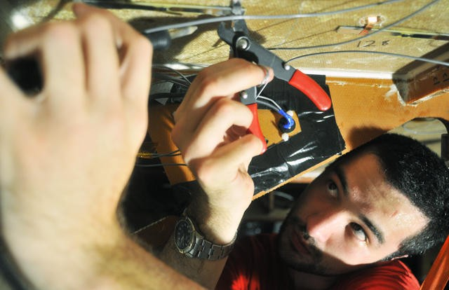 Solar Vehicle Project driver and material science graduate Gareth Westler wires the underbody of the 2010 solar car.
