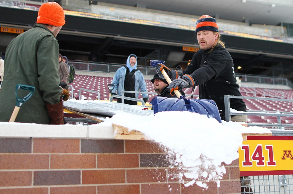 Shovelers pile snow from the bleachers onto chutes leading to the field Wednesday afternoon at TCF Bank Stadium. Workers are busy preparing the stadium for a Monday night Vikings game.