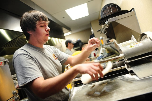 University of Minnesota graduate Tom Alane prepares a pizza Friday afternoon at Campus Pizza.