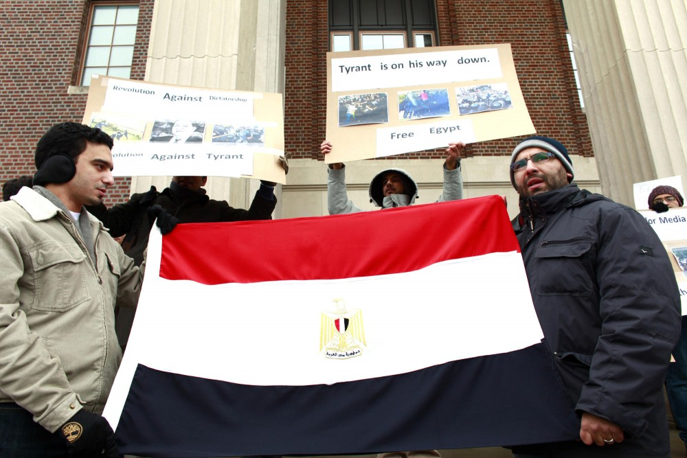 A group of protesters gather outside of Coffman holding Egyptian flags and signs on Friday. Protesters demand current President Hosni Mubarak to step down from his 30 years of dictatorship.