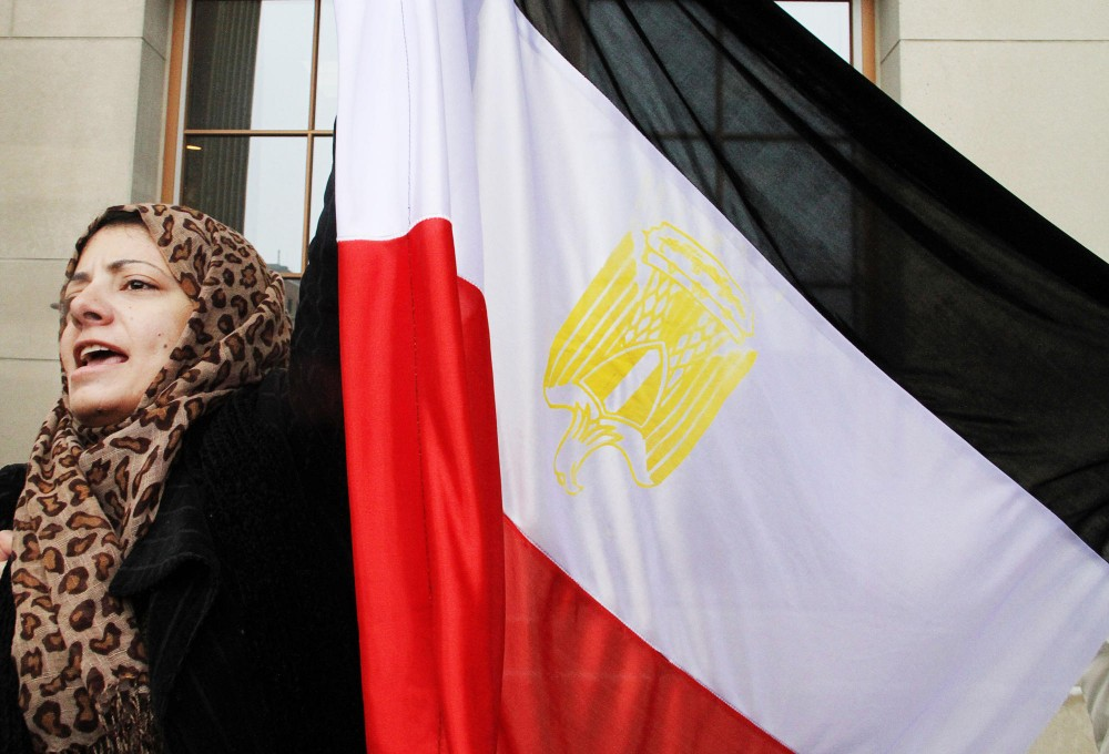 Ansam Elshaish raises an Egyptian flag during a protest in solidarity to current protests in the country's capitol of Cairo, on Friday in front of Coffman Union. Citizens of Cairo are currently protesting calling for an end to the 30 year rule of President Hosni Mubarak.