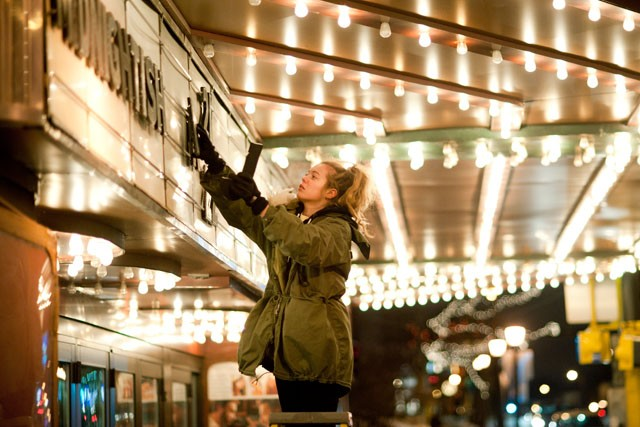 "Uptown Theater employee Danni Nelson puts up dates on the theater's marquee Sunday in Minneapolis. The theater is known for hosting b movie- cult classic films such as Tommy Wiseau's ""The Room."""