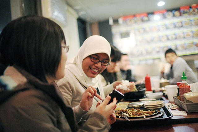 President of the Indonensian Student Association Asa Widiastomo, right, chats with her friend Sistha Darmawan on Saturday at the Korea restaurant.