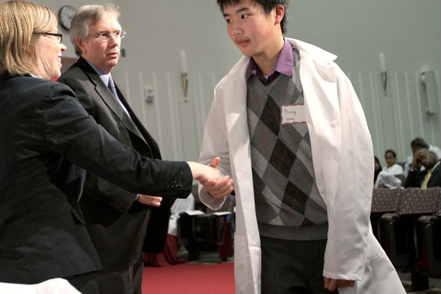 Incoming dentistry major Pheng Vang shakes hands with Health Care Opportunities program specialist Katherine R. Boyum after receiving his lab coat from School of Dentistry Dean Patrick Lloyd on Saturday in the Mayo Auditorium.