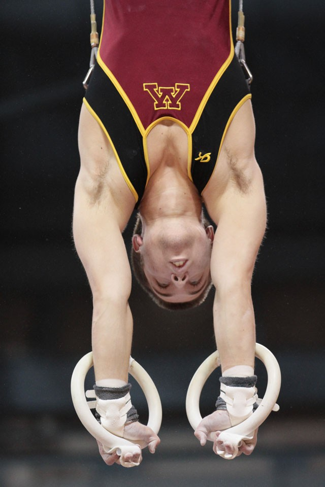 Freshman Steffen Beck  hangs from the rings on Saturday during a men's gymnastics meet against Illinois at the Sports Pavillion.
