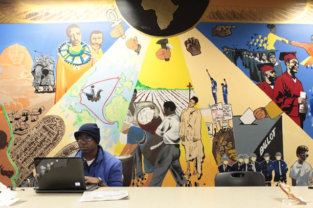 Freshman Lateef Oseni works on homework Thursday evening in the Black Student Union Office in Coffman. The mural behind Oseni was painted in 2004 and shows the timeline of African American heritage.