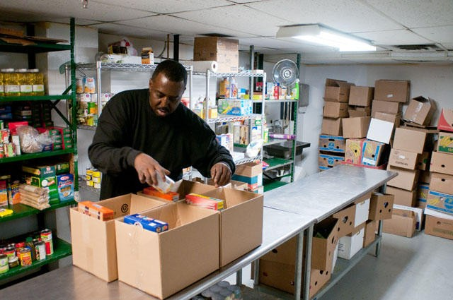 Gregory Burrell, an employee of the Sabathani Community Center, separates food into boxes to be given to people in need on Monday.