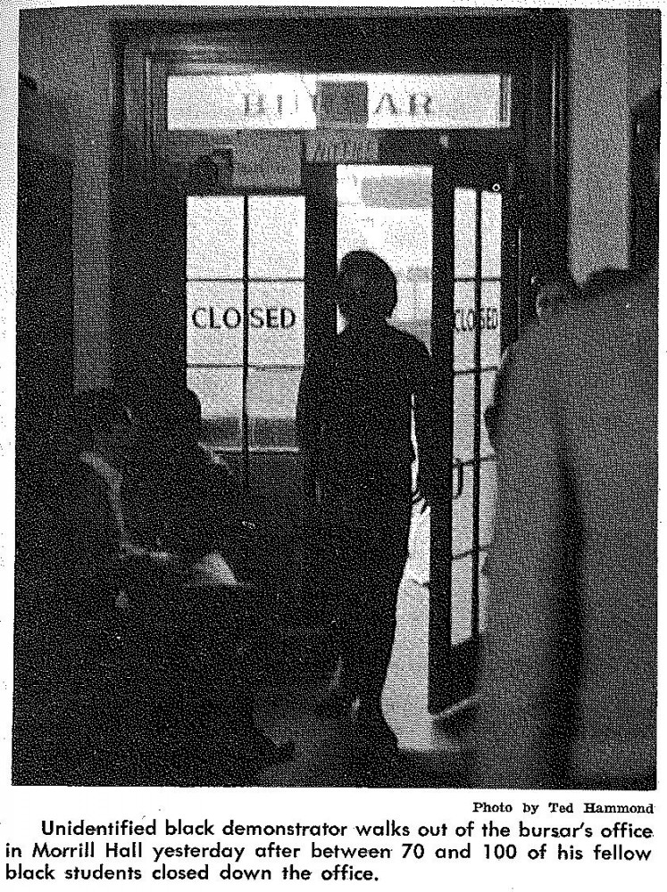 Unidentified black demonstrator walks out of the bursar's office in Morrill Hall yesterday after between 700 and 100 of his fellow black students closed down the office.