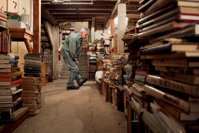 Owner Bill Biermaier looks through books Wednesday in the basement of Biermaier. Biermaier is retiring after running his business for over forty years and still has roughly 50,000 books left to sell.