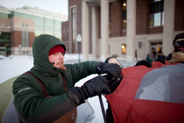 Eco Watch Officer Mikey Weitekamp assembles a tent Monday in front of Coffman Union. The Energy Efficiency Student Alliance held a camp-out to promote Conservation Madness.