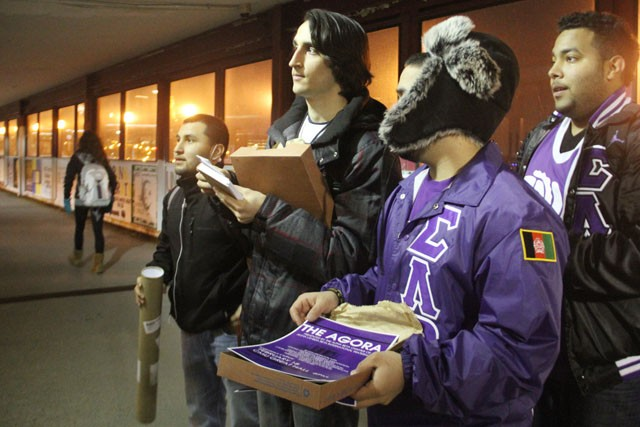 Sigma Lambda Beta members Edwin Bonsil, Tommy DeMarco, Haroon Nekzad and Sherief Elabbady post flyers on the Washington Avenue Bridge on Wednesday in preparation for the Agora 8th Annual Cultural Celebration on Thursday in Coffman Union.