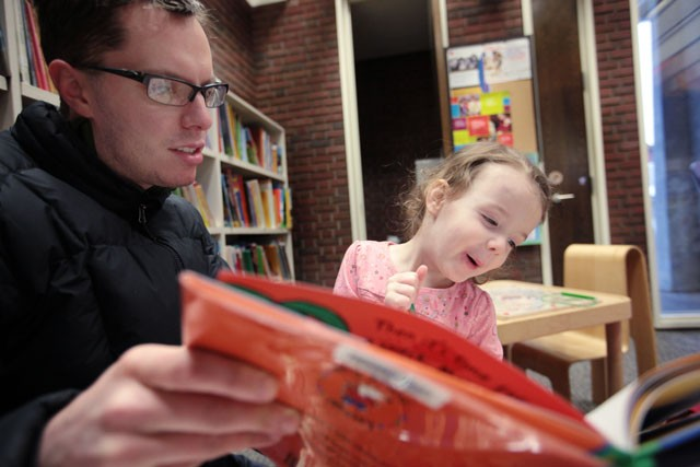 Matt Prekker, left, reads a book to his 2 year old girl Erin on Tuesday at the Southeast library in Dinkytown.  Prekker brings his daughter to the library once a week and plans to continue doing so even if it changes locations.