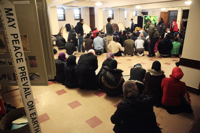 Muslim students and community members gather for noon prayer Friday in Fellowship Hall at Grace University Lutheran Church. Men are required to attend the prayer and around 100 were present on Friday.