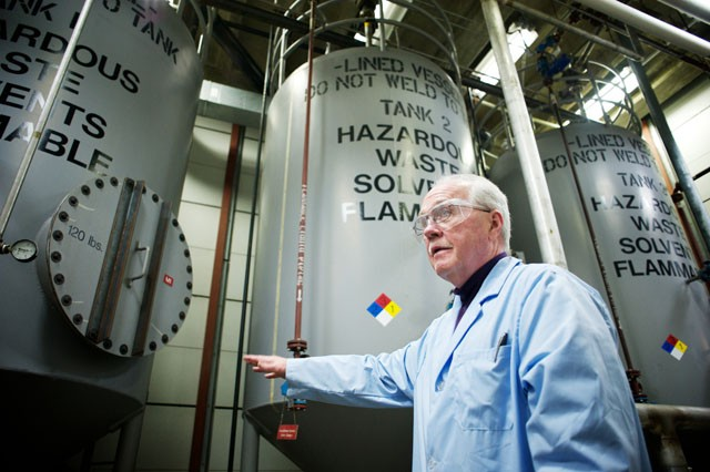 Facility director Andy Phelan stands before three massive tanks that hold liquid chemical waste collected from the university and schools across the state Friday at the Thompson Center for Environmental Management.  Liquid waste is stored in the tanks before being transported by a private company for disposal.