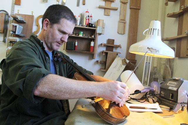 Jong Woutat works on glueing cracks in a violin Tuesday in the Violin Making, Restoration and Repair office located in the University Technology Center. Along with violins, the repair office also works with cellos and violas and has been operating out of the Center for over a year.