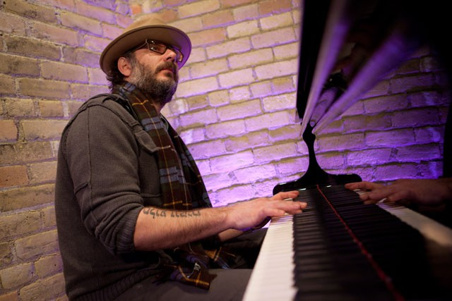 Faculty member of the Institute of Production and Recording Adam Levy plays the piano in a recording studio at IPR Wednesday afternoon. Levy has been commissioned to work with other local musicians for a concert being held at the Cedar Cultural Center on March 6.