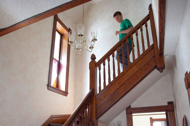 Alumni John Thomason points out a stained glass window in the original staircase Saturday morning in his house in the Como neighborhood. Thomason's house was built by a mason named Donald Cattanach in 1893 and is significant for it's use of roc-faced limestone.