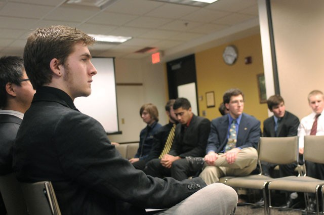 Pledge Josh Adrian listens to Phi Kappa Sigma alumni brothers share stories during the chapter's colonization ceremony on Saturday.