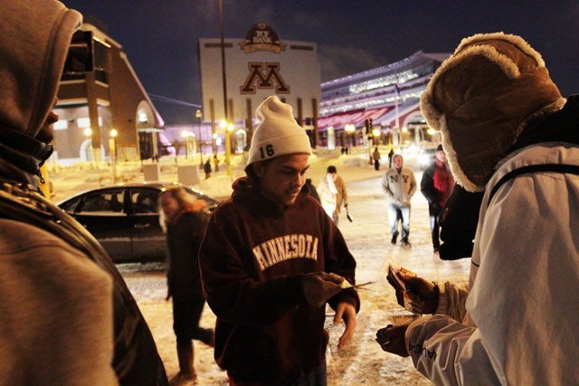A high school student sells four Gopher men's hockey tickets for ten dollars apiece to scalpers on Saturday outside Mariucci Arena.