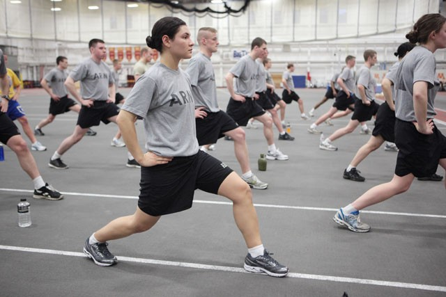 Senior Chloee Daniels-Miller stretches her hamstrings with the rest of the cadets Monday morning in the Fieldhouse.