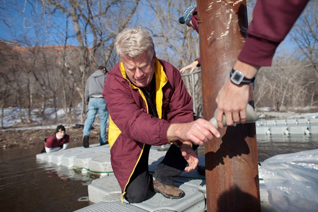 Boathouse manager Tom Perry helps putting the dock together Friday for the rowing team.