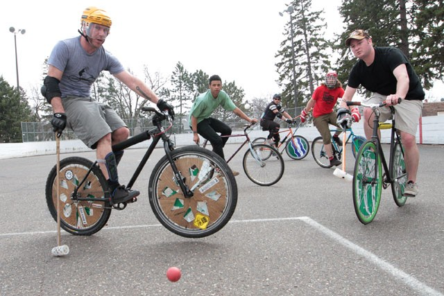 John Gordon, right, shoots the ball past Ebbin Martin, left, during a game of bike polo in South Minneapolis April 10. In addition to practicing three times per week, the group holds games every Saturday for new players to learn the sport.